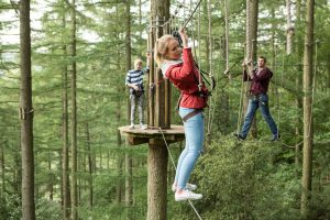 Girl and Boy climbing Peak District go Ape
